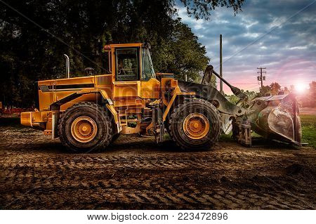 Large bulldozer at construction site, cloudy sky and sunset in background.