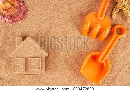 Molded sand house and plastic toys, laying on the beach.