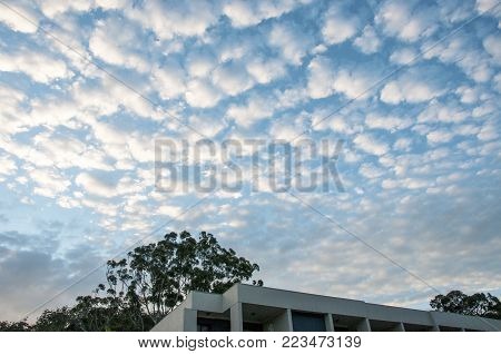 A spectacular inspirational brightly coloured atmospheric cloudy sky cloudscape featuring Cirrus cloud formation in a mid blue sky. Gosford, Australia. poster