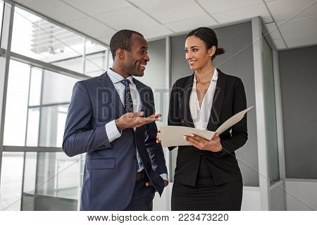 Work together. Cheerful stylish young colleagues wearing formal clothes are standing in office. Attractive woman is holding documents while african man is gesturing with smile