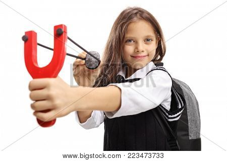 Little schoolgirl aiming with a slingshot and a stone and smiling isolated on white background