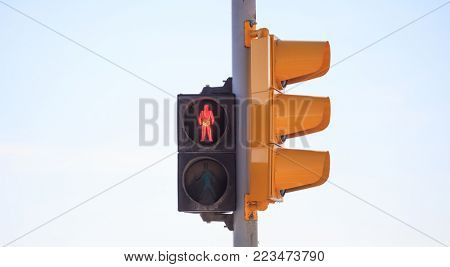 Red traffic light warns pedestrian that is not secure to cross the road. Sky backdrop, space, banner