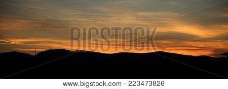 Sunset or sunrise over mountains silhouette with colorful sky backdrop. Panoramic view, banner.