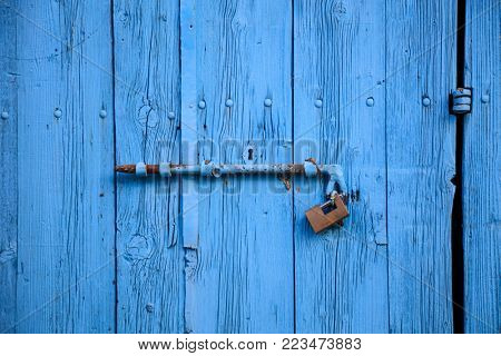 Wooden bright blue, blank, aged door for backdrop. Rusty latch and padlock. Closeup, banner, details