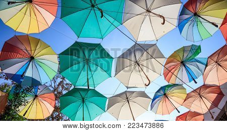 Colorful open umbrellas cover a street at Nicosia, Cyprus. Blue sky and parasols for background.