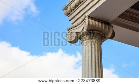 Marble pillar detail of a building facade. Ancient ionic column of white ornate marble. Blue sky, cloud background, under view, closeup, banner