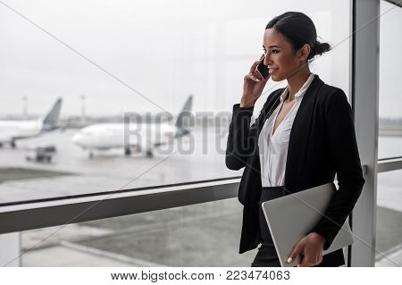 Work everywhere. Side view of young smiling woman is standing at airport lounge with laptop and looking through the window while enjoying conversation on mobile. Copy space and aircrafts in background