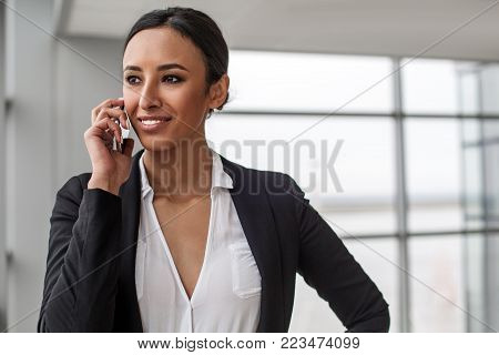 Pleasant communication. Portrait of attractive charming businesswoman is standing in office. She is enjoying conversation on mobile phone while looking aside with wide smile. Copy space