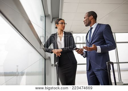 Important negotiations. Low angle of elegant business partners male and female wearing official clothes are standing at terminal lounge with suitcases and talking together