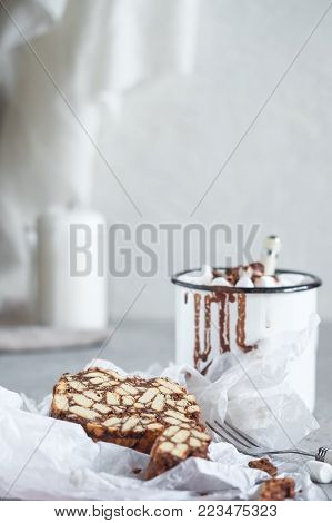Pieces of chocolate cake from cookies and cocoa with marshmallow on bakery paper High key Still life food style Hugge scandinavian nordic with candle