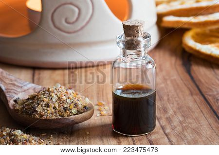 A bottle of myrrh essential oil with myrrh resin on a wooden table with an aroma lamp in the background