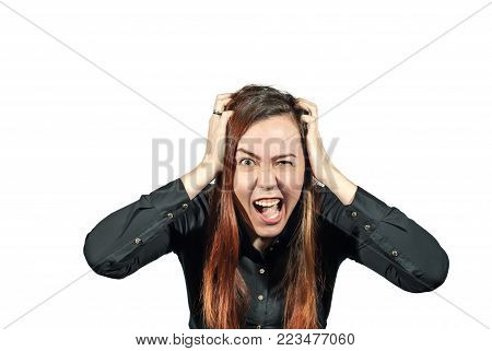 Girl on a white background with extreme expression on her face clasped her hands in her own hair and screams. Stress or hysterics.
