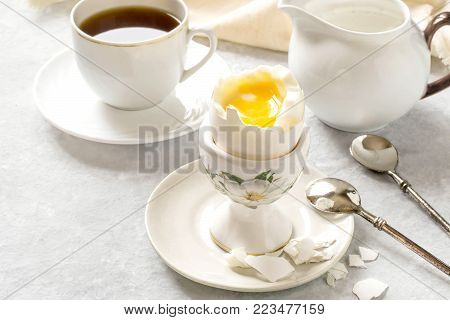 Soft-boiled egg in ceramic egg-cup, coffee and cream. Boiled fresh broken egg with liquid orange yolk, pieces of shell and spoon on plate. Breakfast concept. Selective focus