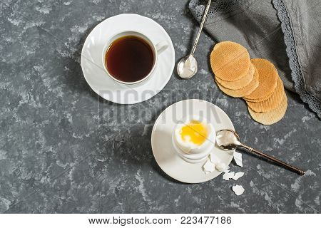 Soft-boiled egg in ceramic egg-cup, cup of coffee and thin crispy corn chips. Boiled fresh broken egg with liquid orange yolk, pieces of shell and spoon on plate. Breakfast concept. Top view