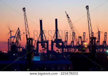 Silhouette of container gantry cranes in the harbour of Hamburg, Germany at sunset.