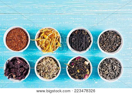 Various dried medicinal herbs and teas in several bowls on blue wooden background from above copyspace.