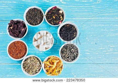 Beautiful circle of colorful tea and herbs on a wooden table with copyspace.