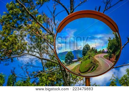 Mirror street sign reflection of the twisting and winding road from the rim top to the shore of Lake Maninjao, Sumatra Island, Indonesia