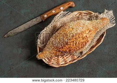Freshly baked homemade whole wheat bread with flaxseeds on wicker tray and coarse jute napkin. Useful dietary bread without yeast. Old iron knife. Greenish-brown textured background