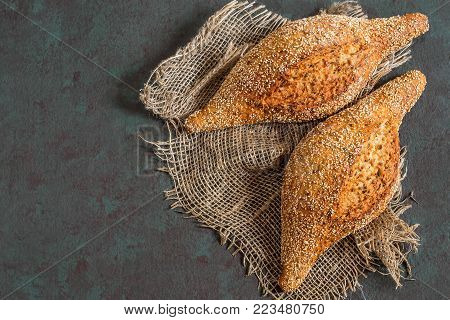Freshly baked homemade whole wheat bread with flaxseeds on coarse jute napkin. Useful dietary bread without yeast. Greenish-brown textured background