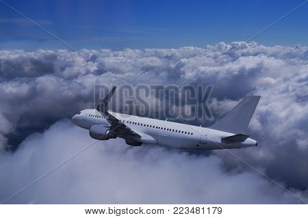 A passenger plane submerges into clumped clouds, above clear sky