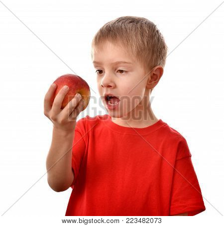 The boy is eating an apple .. A boy's portrait. A cheerful boy. A good mood.