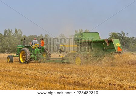 ROLLAG, MINNESOTA, Sept 2, 2017:A field demonstration of a John  Deere tractor pulling a power take-off John Deer Combine 42  at the annual WCSTR farm show in Rollag held each Labor Day weekend where 1000's attend.