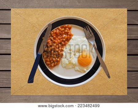 Vegetarian English breakfast with baked beans and fried egg on pub table, top view