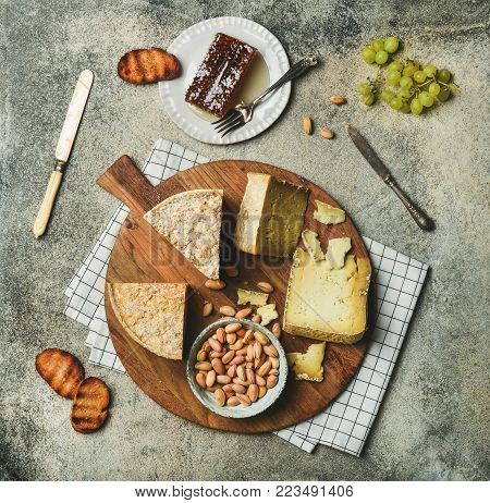 Flat-lay of cheese platter with cheese assortment, green grapes, bread, honey and nuts over grey concrete background, top view. Party or gathering eating concept