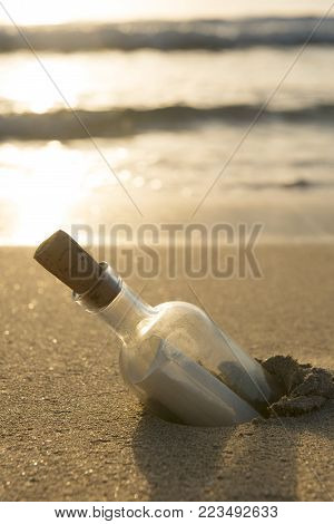 Message in a bottle half-buried in sand with ocean in the background