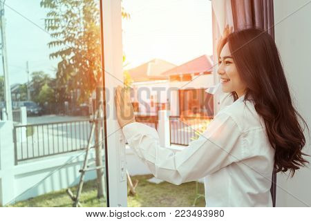 Asian woman wake up in the morning and open window after waking on bed relaxing good day in holiday with sunlight, rear view at living home lifestyle
