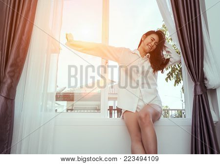 Asian woman wake up in the morning and sitting on window after waking in bedroom relaxing good day in holiday with sunlight, rear view at living home lifestyle