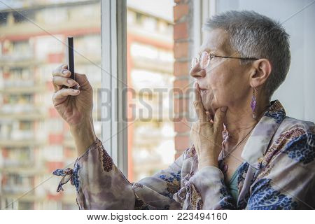 Senior elderly woman having troubles with her cell phone, can't establish the connection