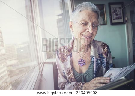 Senior elderly lady looking at some old photos in a photo album, remembering her youth and reliving memories