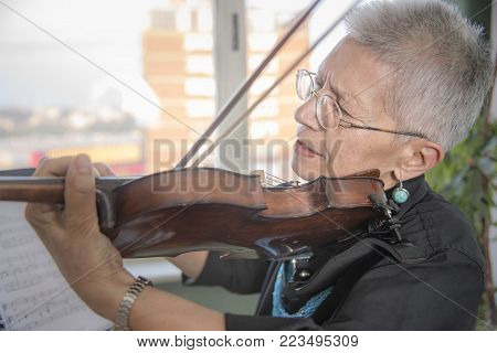 Senior lady playing the violin at her house
