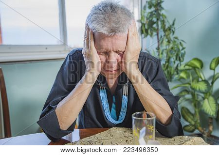Senior elderly lady having a strong and throbbing headache