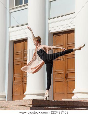 Ballerina in pointe dancing in the street. Performance on the city street. The art of dance. Slender female feet. Classical ballet.