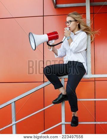 A young attractive girl in a white shirt and glasses is holding a loudspeaker in her hands. She makes an announcement on a megaphone
