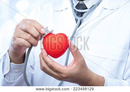 Professional medical doctor holding a stethoscope check up on a red heart ball on blur office in the hospital and bokeh background. Concept of health care.