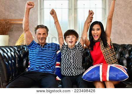 Family Concept. Family is happy in the house. The family is playing in the living room. The family loves each other happily. Families are watching television (TV).