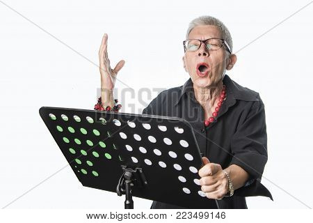 Senior woman practicing her singing skills from a stack of musical sheets