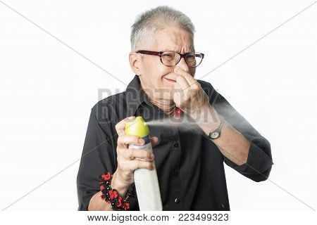 Senior woman spraying air freshener all over, disgusted by the stench of the room