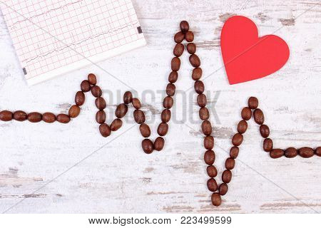 Cardiogram line made of coffee grains and electrocardiogram graph on rustic board, ecg heart rhythm, medicine and health care concept