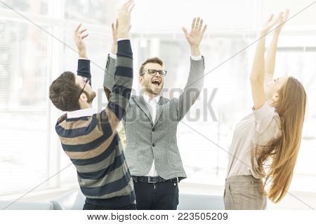 jubilant business team standing in a circle, hands up in rejoice success.the photo has a empty space for your text.