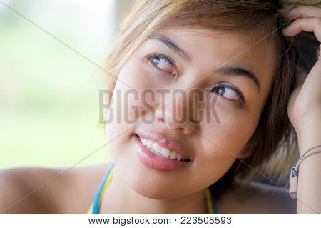 close up portrait of young happy beautiful Asian woman from Indonesia looking thoughtful and pensive daydreaming and thinking at outdoors coffee shop