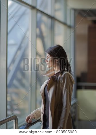 Confident successful business woman standing next to a large window of a modern office.