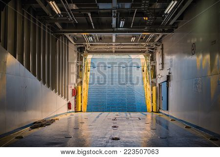Bow ramp of and garage for the cars inside of ferry. View from inside