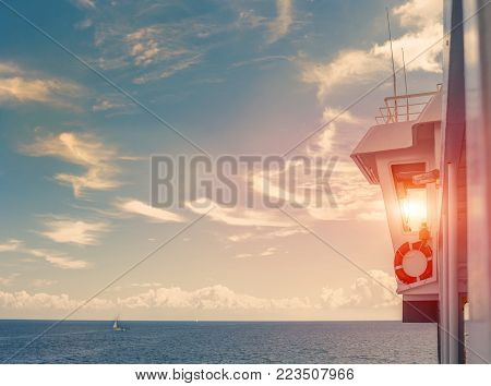 Outdoor view on captain's cabin, glass control room and sunset sun through window