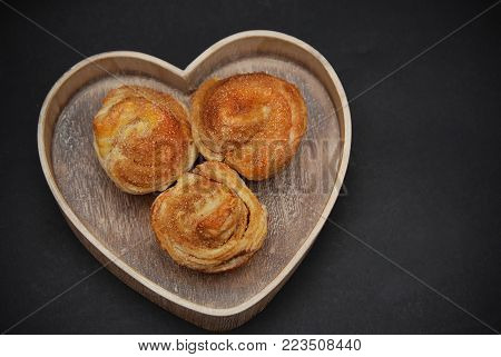Three Cinnamon Sweet Roll Buns in Wooden Heart, Over the Black background