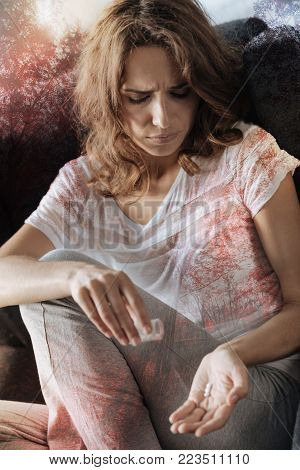 It might help. Desperate unhappy woman sitting at home and being in sorrow while taking pills